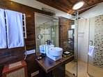 Bathroom attached to the third bedroom on the first floor is done in brown and beige tiles
