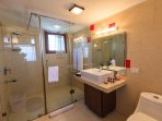 Bathroom attached to the attic room with white tiles with shower and all amenities