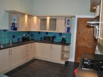 Fully equipped kitchen with a washing machine, oven, toaster, kettle and microwave.