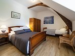 Large bedroom with single and large double bed, air conditioning and private bathroom with bath
