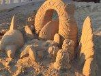 Beach artist creates intricate sculptures.