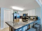Fully equipped kitchen with additional seating at the bar area