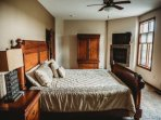 Luxurious master bedroom with king bed and gas fireplace.