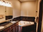 Dual vanity sinks, corner jetted tub, shower stall - all in the master bath.