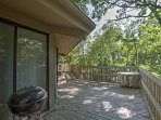 The second-floor condo features a private oversized balcony surrounded by towering trees.
