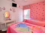 Princess themed bedroom with wall-mounted TV and handy dressing table