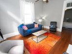 The living room space features a 3-seater sofa and vintage leaether rocking chair.