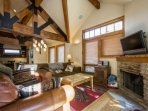 The living room is well equipped with comfortable fabric and leather furnishings, HDTV, fireplace, coffee table and...