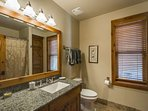 The second full bathroom features a long granite counter top with vanity, bathtub and shower.