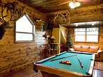 Game room with pool table, tv, poker table and sleeper sofa.