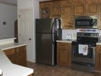 The kitchen has light wood cabinetry and stainless appliances.