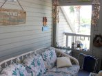The screened in porch is decorated with coastal themed rattan furniture.
