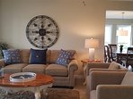 Seating group in living room with pull out sofa, 2 swivel arm chairs and deep pile area rug; partial view of dining...