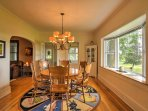 The large dining room features a bay window, offering views of the lush landscape.