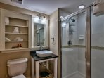 The full guest bath has modern vessel sinks and tiled stand up glass shower - common area bathroom.