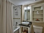The en suite master bathroom has a modern vessel sink and upgraded shower head.