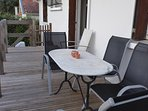 Table and Chairs on Decking Overlooking Terrace and Pool