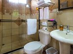 Condo 2: Shared bathroom with tiled shower.