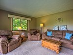 The living room features plush arm chairs and a large sofa.