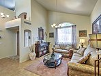 Step through the front door and into the formal sitting area with vaulted ceilings and 2 plush couches.