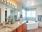 The en-suite master bathroom offers a walk-in shower and separate tub.