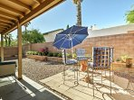 Feel the sunshine on the back patio with outdoor furniture and an umbrella.