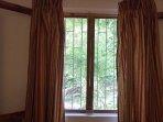 Via la fenêtre moustiquaire, la chambre donne sur le bush