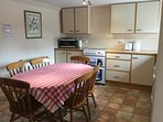 Fully fitted kitchen with cooker and hob, microwave, fridge freezer and spacious dining area.