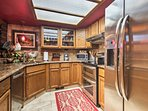 The fully equipped kitchen boasts stainless steel appliances, granite countertops and gorgeous wood cabinetry.