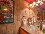 This powder room offers tumbled marble walls, a vessel sink, cherry wood cabinets and granite counters.