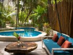 Deck furniture around the pool. Shaded by palms.