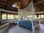 Casa Mandala master suite with king bed, jungle views, ensuite, traditional palapa roof.
