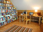 The upper floor has an open mezzanine with a library and desk space, complete with printer.