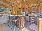 Fully Equipped Kitchen with Granite Countertops, Stainless Steel Appliances and Farm Sink, and Bar Seating