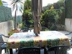 Gran mesa con sillas y sombrilla para disfrutar de los desayunos y de las comidas