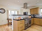 Open plan bespoke designer kitchen with dining area, secondary television area and utility room off
