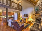 The living room boasts hardwood floors, vaulted ceilings, and a massive stone fireplace.
