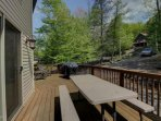 Deck with picnic style table, propane BBQ grill and lounge chairs