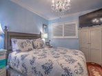 Queen bedroom with HDTV and in-room air conditioner for comfort.
