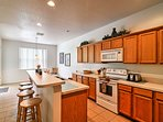 The fully equipped kitchen comes complete with natural wood cabinetry and plenty of counter space for cooking ...