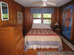 Large pine bedroom with  queen bed on one end and bunk beds on other end.