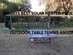 Out door table tennis tables next to shade cover of solar heated pool.