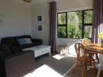Bright living/dining room with harbour and bush views