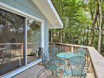 Large glass sliding doors open from the upstairs living room to a lush view of the surrounding forest.