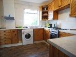 Fully fitted kitchen area leading to large decked garden area with outdoor seating and summer house