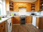 Fully fitted kitchen area leading to large decked garden area with outdoor seating and summer house.
