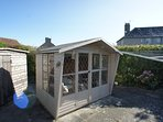 There is a large sunny decked and paved garden to the rear of the house with summer house