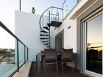 Second floor terrace and spiral stairway up to the roof terrace