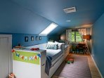 Fanciful bedroom with two twin beds and pullout trundles and full loft bed