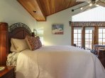Master bedroom with comfy bed and vaulted ceilings.